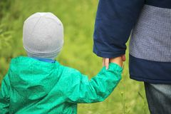 A little boy holding his mom`s hand. A boy walking oute holding his mother hand royalty free stock image