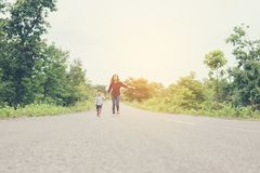 Little boy holding his mother hand running on the street enjoy g. Ood time together look so nice royalty free stock image