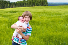Little boy holding his newborn sister Royalty Free Stock Photos