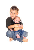 Little boy holding his three weeks old brother. A little boy sitting on the floor and holding his new three weeks old Stock Photography