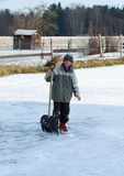 Little boy holding ice-cleaner on pond Royalty Free Stock Images