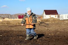 A little boy holding a large rake in his hands helps to work on the ground royalty free stock photos