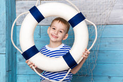 Little boy holding a lifebuoy and laughs Stock Image