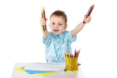 Little boy holding a lot of colored pencils Royalty Free Stock Images