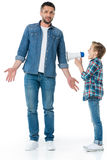 Little boy holding megaphone and screaming at father standing Stock Photography