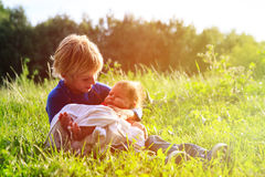 Little boy holding newborn sister in summer nature Royalty Free Stock Photos
