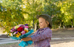 Little boy holding out a floral bouquet Stock Images