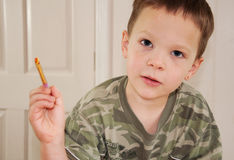 Little Boy Holding Paint Brush. This little boy is holding a paint brush loaded with paint as he's enjoying his hobby as a budding young artist Stock Photos