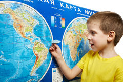 Little boy holding paper airplane on world map Royalty Free Stock Image