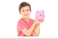 Little boy holding a piggybank Stock Images