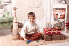 Little boy holding present box in Christmas interior Stock Photo