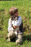 Little boy holding a puppy royalty free stock image