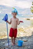 Little boy holding red five point starfish and bucket in his han Stock Photo
