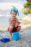 Little boy holding red five point starfish in his hands on the b Stock Photos