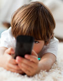 Little boy holding a remote lying on the floor Royalty Free Stock Image