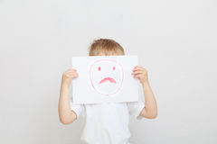 Little boy holding sad face mask Stock Image