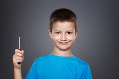Little boy holding screwdriver on grey background. Little caucasian boy holding screwdriver on grey background Royalty Free Stock Images