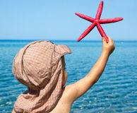 Little boy holding sea star Stock Photos