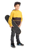 Little boy holding a skateboard. Full length portrait of a little boy holding a skateboard and looking at the camera isolated on white background Royalty Free Stock Photography