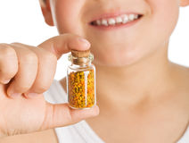 Little boy holding small bottle of pollen Royalty Free Stock Image
