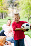 Little boy holding a soccer ball. With his family in the background Stock Images