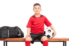 Little boy holding a soccer ball seated on a bench Stock Image