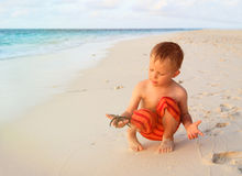 Little boy holding starfish on sunset beach Royalty Free Stock Images