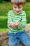 Little boy holding sunflower seeds in garden Stock Images