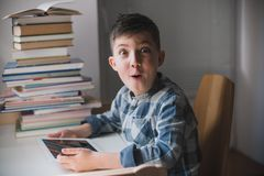 Little boy is holding a tablet and looks suprised. royalty free stock photography