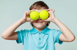 Little boy holding tennis balls instead of the eyes, smiling Stock Images