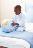 Little boy holding a terrestrial globe. Lying on his bed stock image