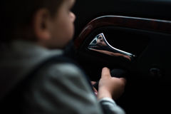Little boy holding on to the door handle of car Stock Image