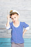 Little boy holding on to his cap royalty free stock photos