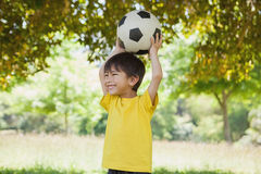 Little boy holding up football at park Stock Image