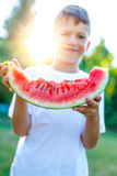Little boy holding watermelon slice in sunset Stock Images