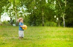Little boy holding yellow ball Stock Photos