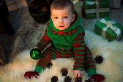 Little boy holds Christmas ball in hand, sits and plays by pine royalty free stock photos