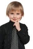 Little boy holds finger on his cheek Stock Images