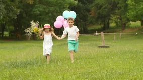 Little boy holds the girl by the hand and they run along the lawn together. Slow motion. Little boy holds the girl by the hand and they together run along the stock footage