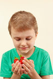 Little boy holds handful of sweet strawberries Royalty Free Stock Images