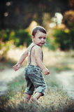 Little boy holds in his mouth lollipop on a stick outdoors royalty free stock photos