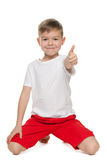 Little boy holds his thumb up. A little boy holds his thumb up against the white background stock photo