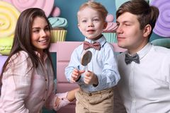 Little boy holds lollipop, young mother and father Stock Photography