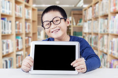 Little boy holds tablet with empty screen. Cute schoolboy wearing glasses in the library and smiling at the camera while showing a digital tablet with blank Stock Images