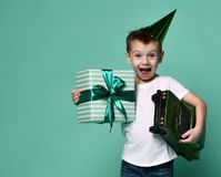 Joy of birthday. Little boy holds a toy car and a box with a gift on a light background. birthday party royalty free stock photography