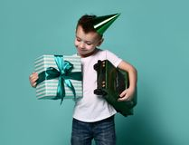 Joy of birthday. Little boy holds a toy car and a box with a gift on a light background. birthday party stock photos