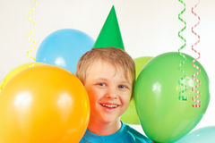 Little boy in holiday cap with festive balls and streamer Royalty Free Stock Photo