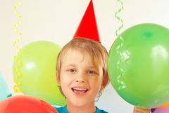 Little boy in holiday hat with festive balls and streamer Stock Photo