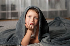 Little boy at home on the carpet Stock Images