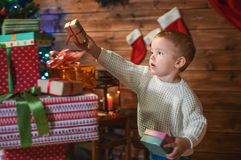Little boy at home with a Christmas tree, presents and candles. Celebrating christmas Stock Photos